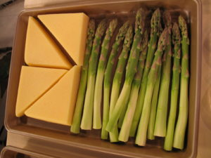Polenta wedges and asparagus are ready to be broiled.
