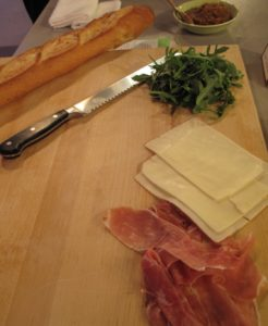 The ingredients for a great flavor-filled sandwich - fig jam, arugula, sliced asiago cheese, and prosciutto assembled on a baguette