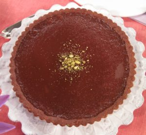 Milk Chocolate-Pistachio Tart - You'll find pistachios everywhere in this dessert - embedded in the crust, in a paste layered beneath the milk-chocolate filling, and in a dusted coating on top.