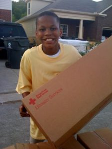 This young boy got busy and helped to pass out the Red Cross supplies.