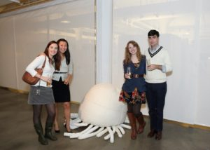 """Guests posing next to Duane Stapp's """"Soft Contribution"""", one of three pieces he showed this year."""