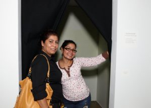 """Adriana Weisberg and Ana Velasquez in Erin Furey, Tadd Kroneck, and Anthony Luscia's """"Glow Room"""" (a phosphorescent room where guests could """"paint with light"""" using lasers, flashlights, and camera flashes)"""