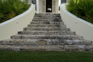 "The so-called ""welcoming arms"" staircase, made of mottled coral stone, leads up to the house from the garden."