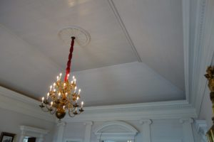 The tray ceiling - The nineteenth-century brass chandelier is English.
