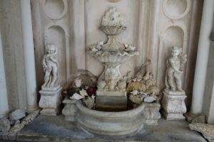 This fountain is located in the home's porte cochere, the covered entrance, where vehicles could pass and drop off occupants. John brought back the fountain from Venice. The trompe l'oeil wall was a work done by John. All the shells were collected during John and Bill's travels.