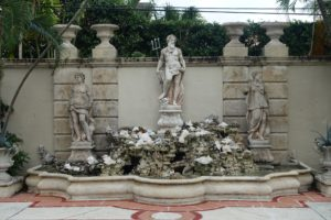 This grotto fountain is not original to the house. John added the fountain made with coquina, soft limestone made from jagged shells, the urns and other figures. The wall itself was done by Fatio.