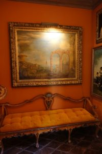 This is another painting by John. The bench is an 18th century piece from Venice. They sit in the home's powder room.