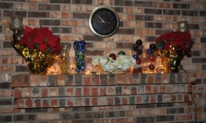 Christine Brown from Fittstown, OK was inspired to decorate her fireplace mantle using pointsettia garland, candles, and white lights.