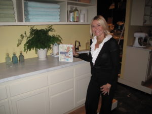 Susan Magrino - my publicist - posing on the utility room set with a copy of my Homekeeping Handbook.