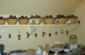 In the kitchen, yellow-ware bowls were filled with pine-cones and ornaments hung from the peg hooks.