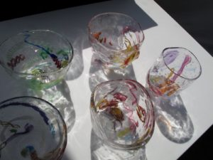Each of these cups are all one of a kind made up from brightly colored and patterned glass elements.