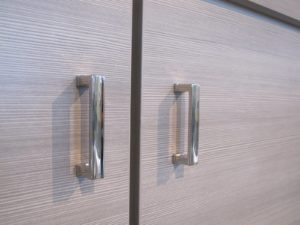 Horizontal wood grain and sleek handles create the sensibility of an architect's custom-built design.