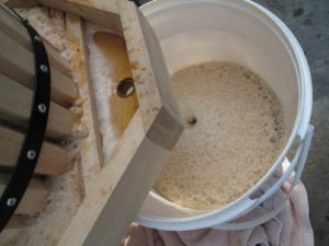 As the pulp is pressed, the sweet cider flows out, filling a bucket beneath.