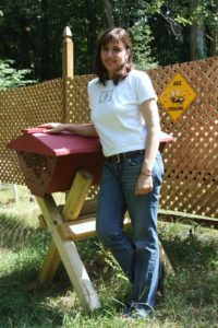 This is Marina Marchese standing next to a top bar hive occupied by some of her Italian honeybees.
