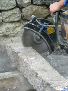 This saw sprays water into the blade guard, catching most of the generated stone dust, dropping it to the ground.