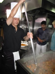 This cook, with very strong arms, is in charge of stirring the   the curry base.