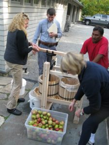A 2 X 4 provides Laura with more torque for pressing.  Pete keeps grinding as I keep feeding more apples.  Shaun was fascinated, as he had never seen this process before.