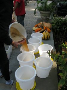 Pouring the cider into clean, one-gallon containers being careful to leave the foam behind
