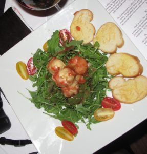 This salad is tempura fried goat cheese drizzled with a raspberry vinaigrette over baby arugula - very tasty.