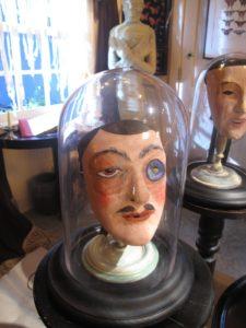 Strange masks beneath glass domes