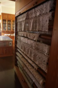 Laundered and pressed tablecloths are stored on wooden poles and stored beneath a rolling tambour.