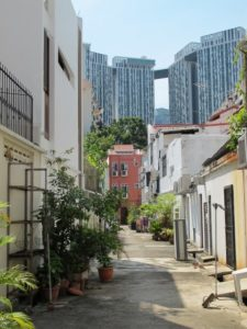 A back alley with historic homes juxtaposed with modern skyscrapers
