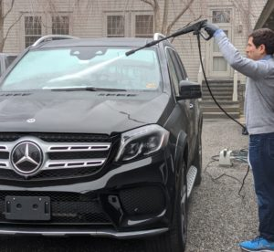 Here, Andres sprays the windshield and gets any debris out from under and around the wipers. Always try to point the sprayer downward, so water does not get into the car or under any of the car's protective seals.