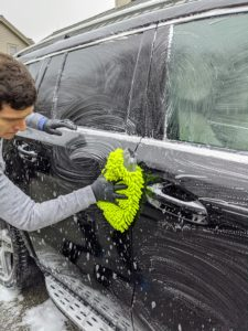 He soaks a large mitt in soapy water and rubs the car down in sections, starting from the top and working to the bottom. Don't use a brush on the car body - it may leave little scratches.