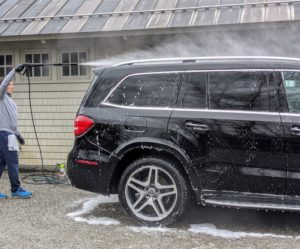 When it is time to rinse, Andres circles around the car several times with the pressure washer. Washing the car from the top down will allow soap to drip over lower sections of the car.
