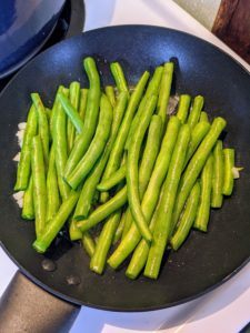 In another skillet over medium heat, she adds the remaining chopped garlic and cooks the green beans, stirring occasionally, until they are tender and browned in spots.