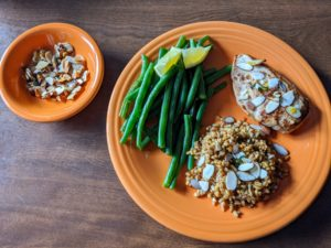 The chicken, grains, and green beans are served with the almond-herb gremolata.