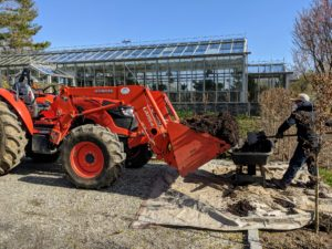 This is my new Kubota model M7060HD12 tractor – a vehicle that gets lots of use at the farm every day. It is used for pulling or pushing agricultural machinery or trailers, for plowing, tilling, transporting and so much more. Here, it is used to transport a bucket load of composted manure for the garden bed.