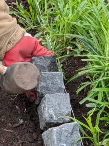 Chhiring uses a mallet to pound the bricks into place, so they are not damaged in the process.