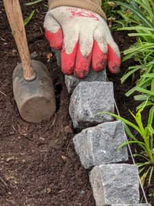 Once the brick is positioned, the soil is pushed around it until it is secure.