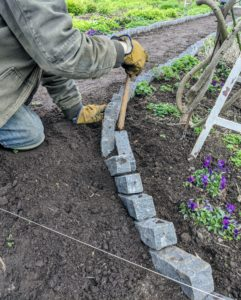 He also lays one brick horizontally where the two angled ends meet, so there is a consistent barrier between the path and the garden bed.