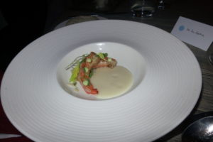 This presentation was blue shrimp with a vegetable puree and peas.