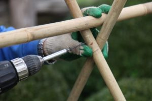 Chhewang screws the bamboo posts together, forming a joint.