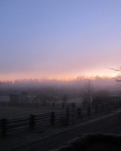 The sunrise, coming into focus and illuminating the farm