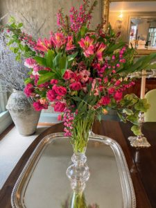 This bold pink and green arrangement is in my smaller dining room. When making arrangements, cut all green and woody stems at a 45-degree angle. This prevents stems from sitting flat in the bottom of the vase and creates a large surface area, ensuring maximum water absorption.