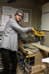 Sean Ennis from Design and Fabrication cutting with a circular saw