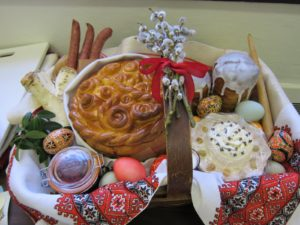 This basket lined with a traditional Ukrainian embroidered cloth if filled with symbolic foods of Easter ready to be blessed, including kielbasa, horseradish root, beet and horseradish condiment, flavored butter, babka, Pysanky eggs, and the paska.