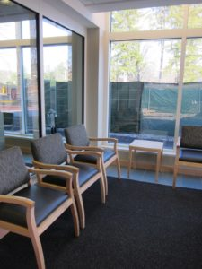 The carpeted waiting area is equipped with comfortable chairs.  Big windows allow for lots of natural light.