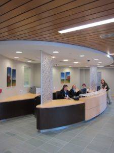 Concierges sit at the reception desk, meeting people as they come in.  There is a separate entrance for people who arrive by ambulance.  Notice the natural healing elements - a soothing slate floor, decorative glass panels, and plenty of warm wood.