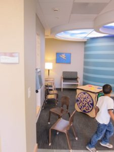 A fun play room for children is found right off of the main waiting room.  Notice the calming ceiling with sky panels.