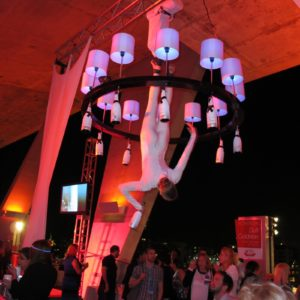 Men and women were suspended from the ceiling performing an aerial act.