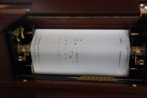 The music score is programmed onto the paper by means of perforations.  Air is sucked through the perforations into the tracker bar, triggering the correct piano keys.