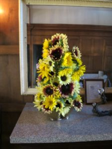 Two arrangements of mixed sunflowers adorned the side table at the front entrance.