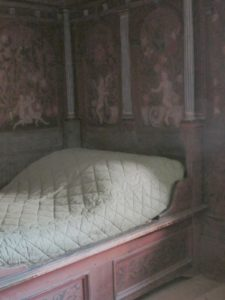 A small built-in bed in one of the bed chambers - Notice the painted scenery.