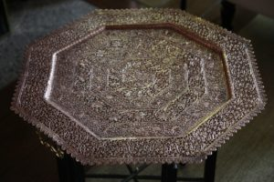 This tabletop is an ornate copper tray from India.
