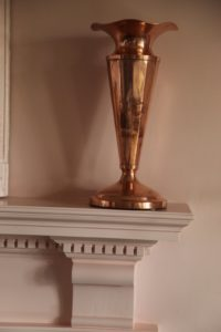 This is one of a pair of copper vases on the mantelpiece, which soaks up and reflects the pink surroundings.